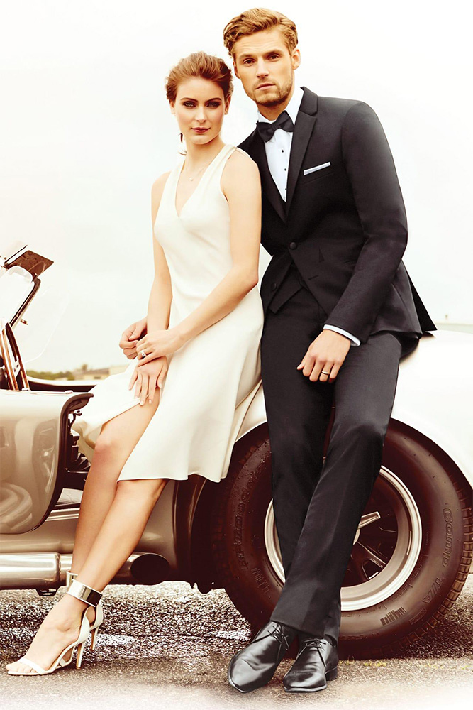 man and woman in formal wear leaning against a car